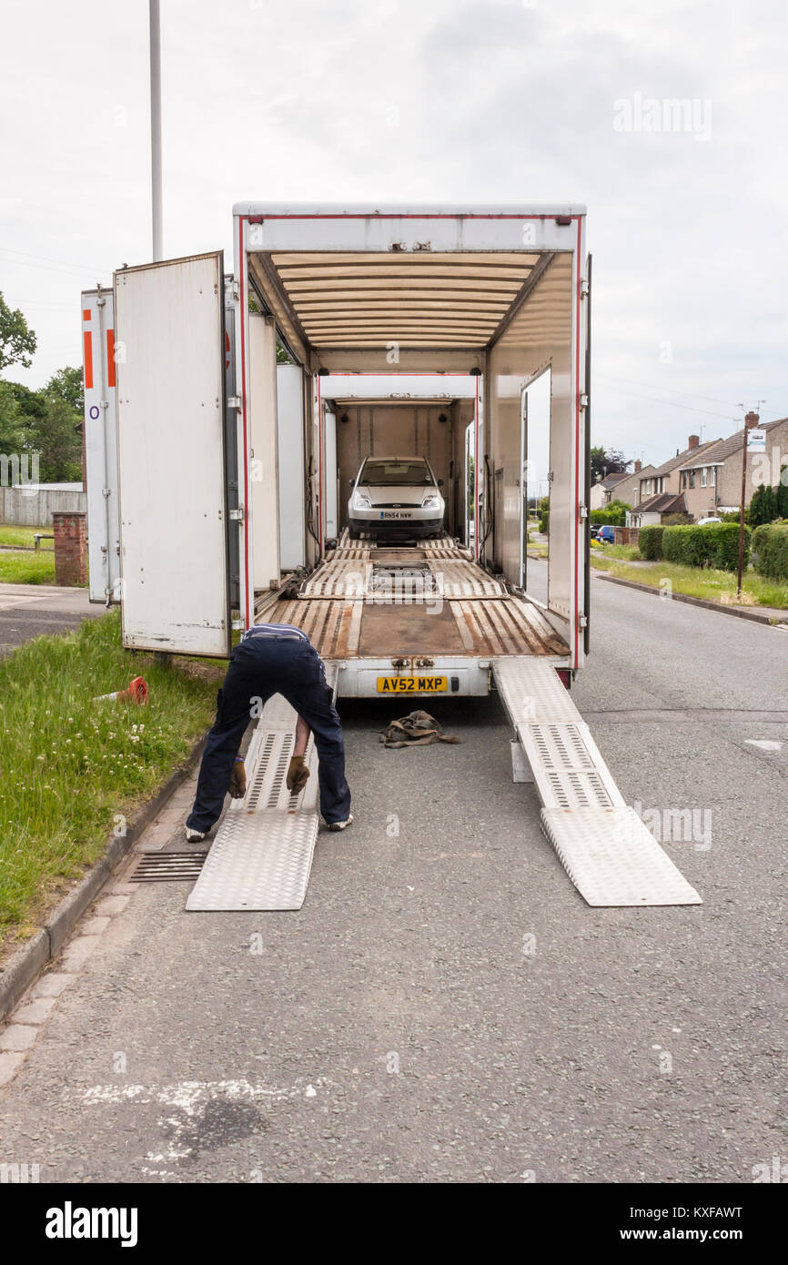 Worker for Ontime Automotive removes recovered breakdown vehicle from HGV on UK street - Stock Image