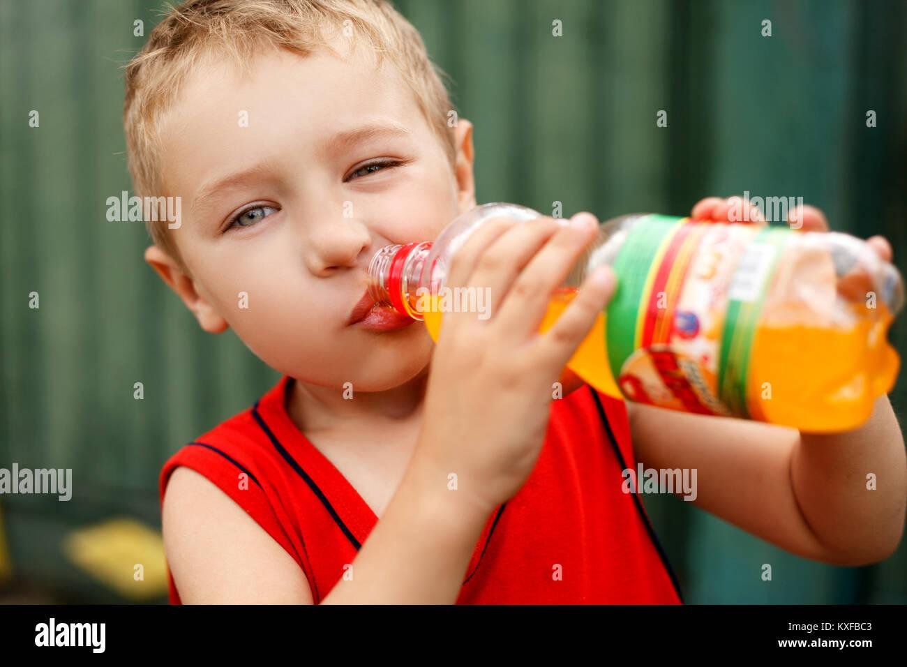 Child drinking unhealthy sweet bottled soda - Stock Image