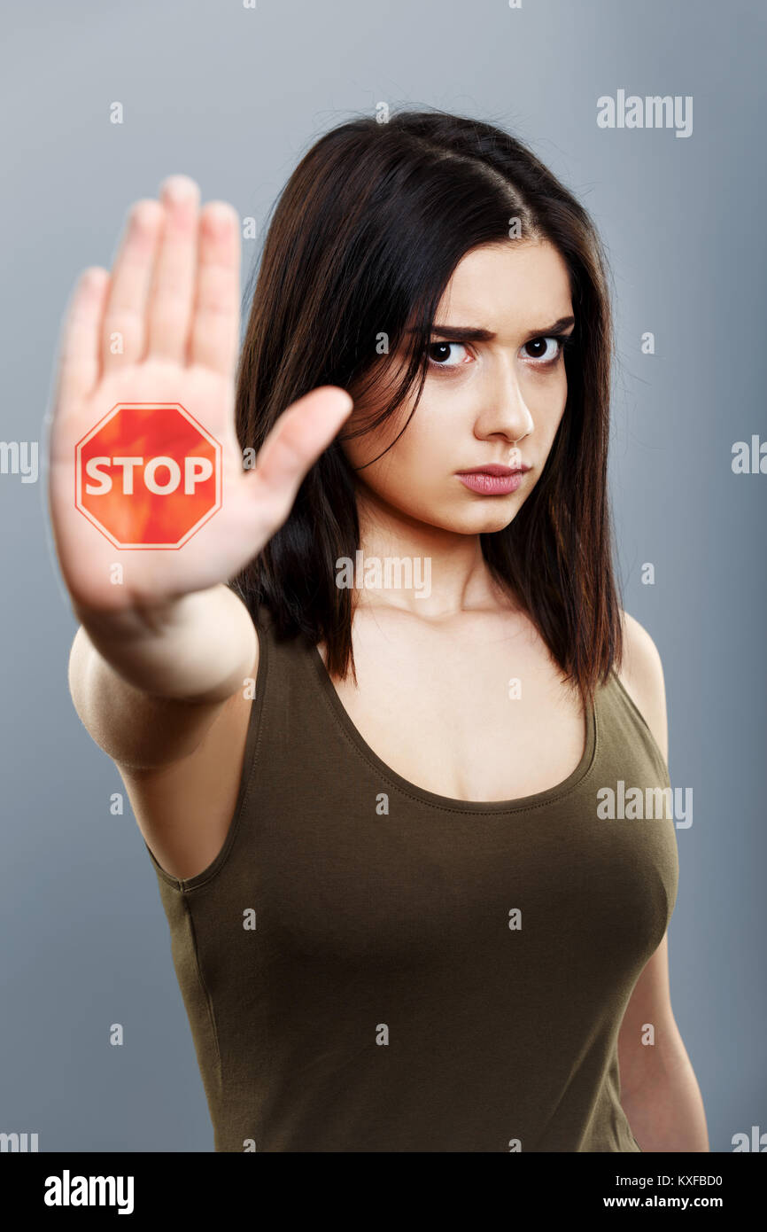 Domestic violence and abuse concept. Upset woman showing hand stop sign - Stock Image