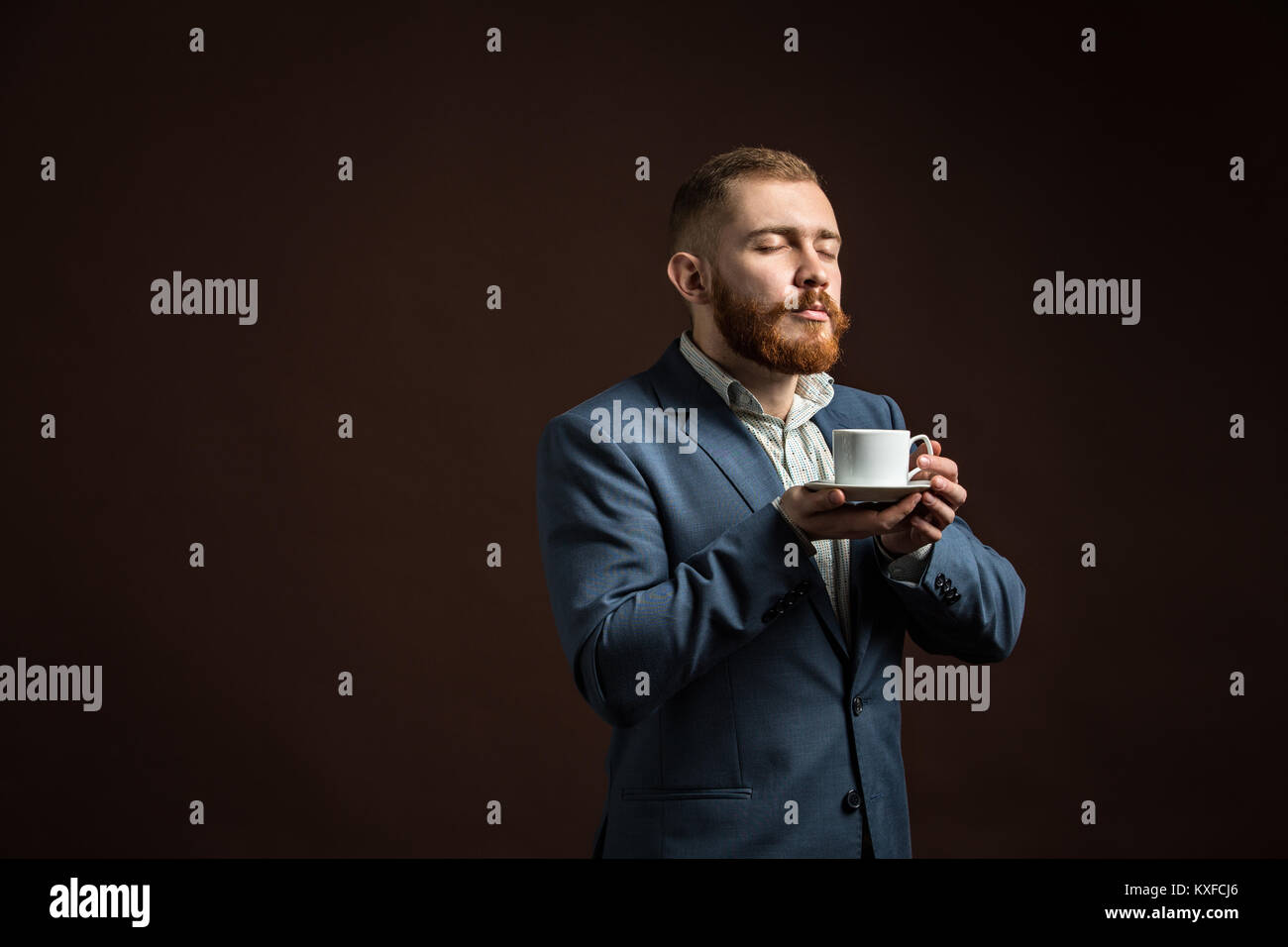 Handsome bearded man enjoying smell of coffee - Stock Image