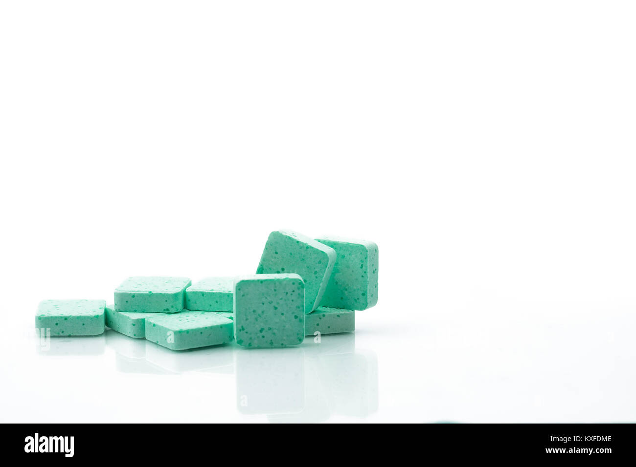 Macro shot to show detail of green medical lozenges for relief cough, sore throat and throat irritation on white - Stock Image