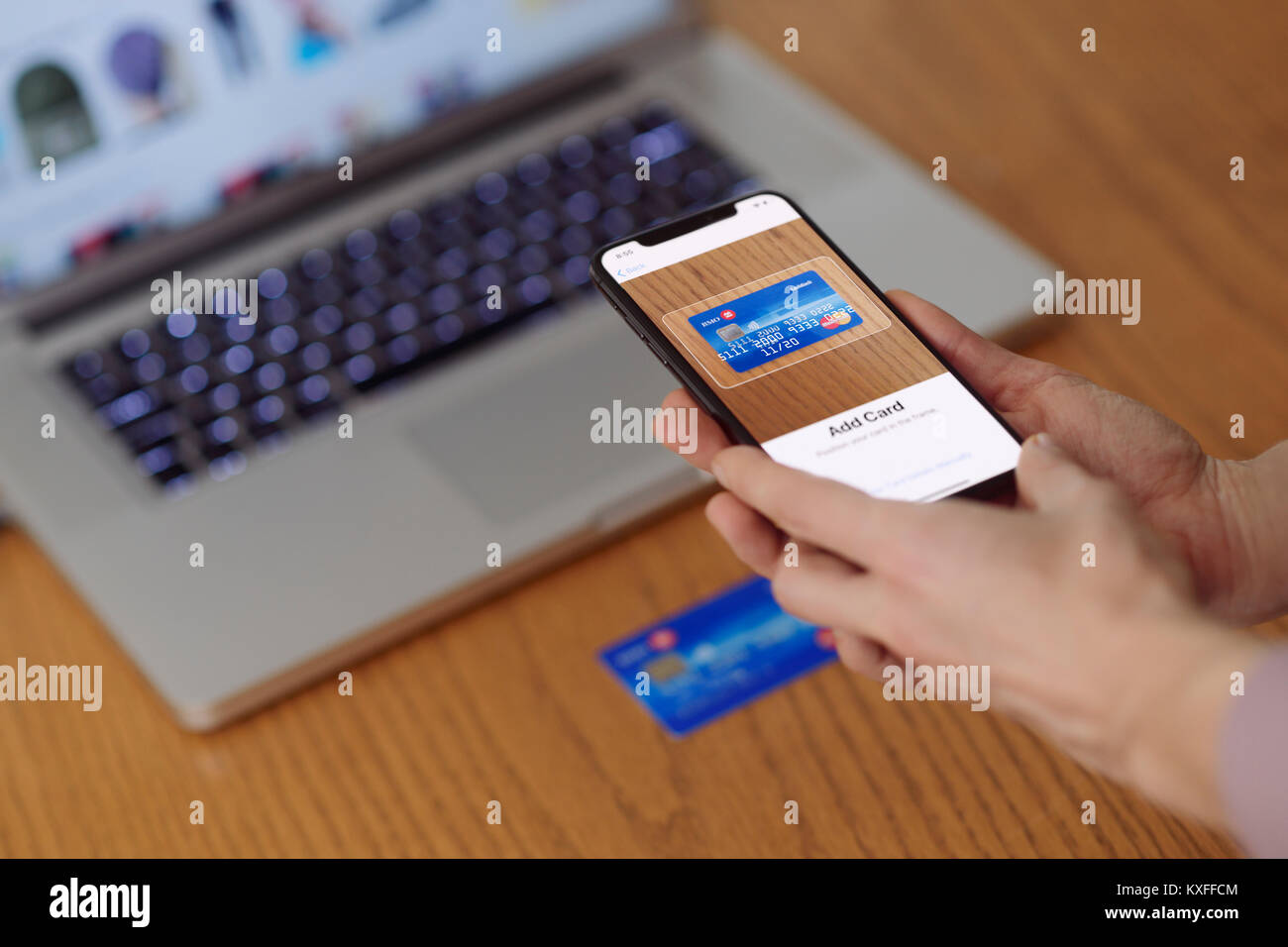 Woman with iPhone X in her hand scanning a credit card with Apple Pay, Apple Wallet electronic payment app Stock Photo