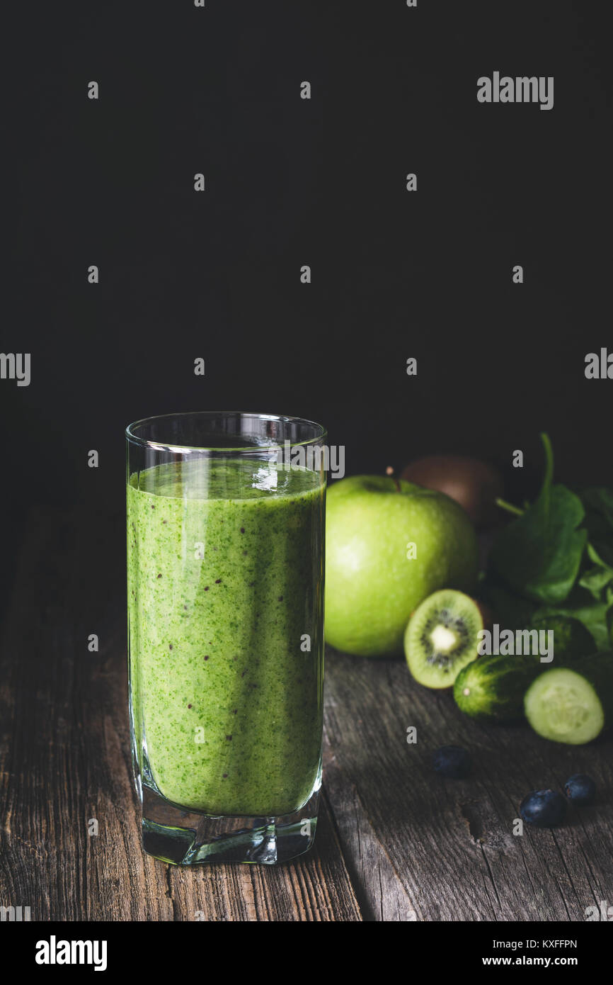 Green smoothie detox juice in glass on wooden table. Toned image, dark background - Stock Image