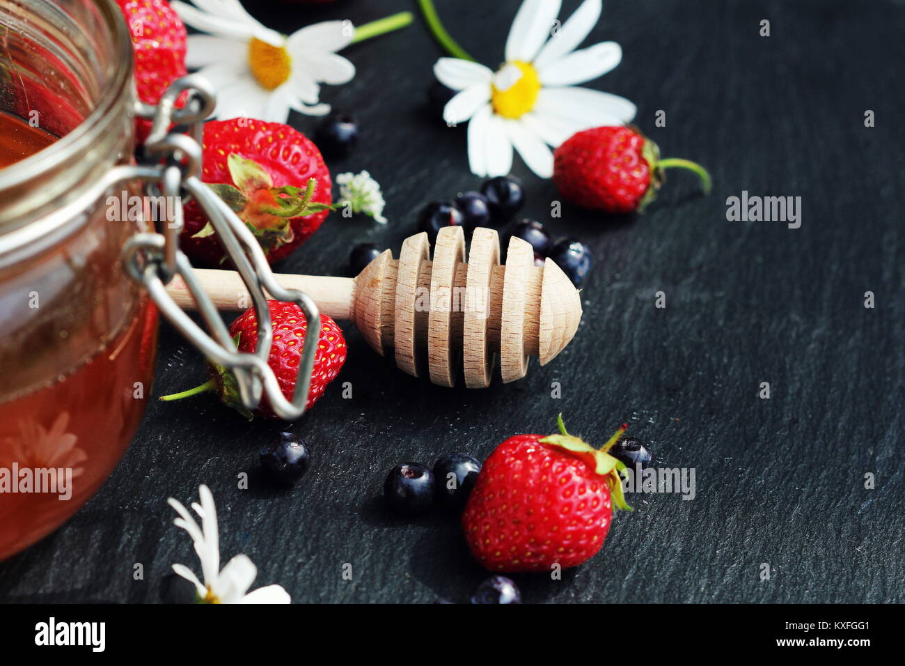 Glass with honey raspberry and flowers chamomiles on dark background. Wooden dipper . Selective focus - Stock Image