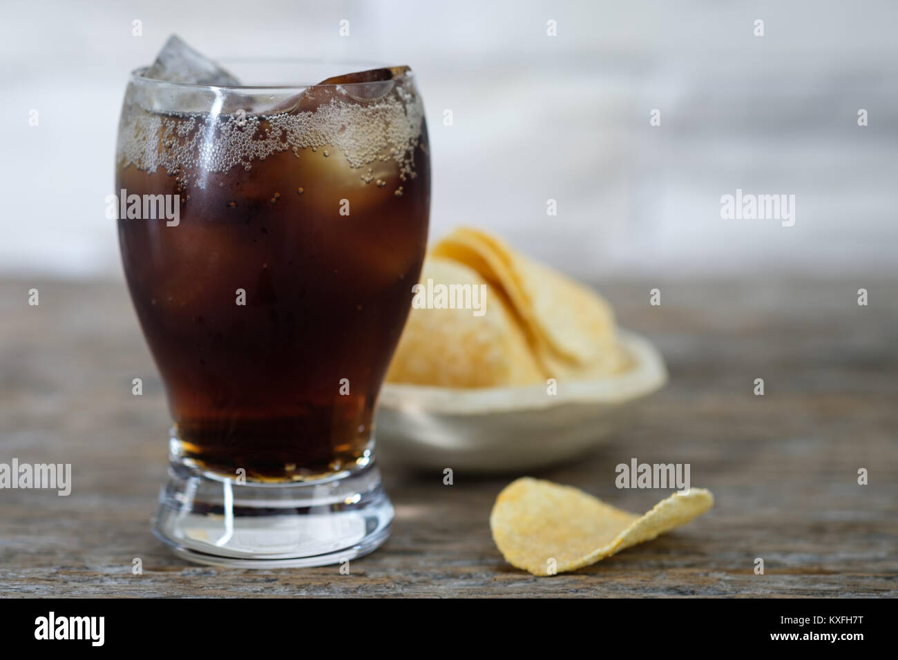 Glass of cold sparkling water and potato chips on wooden background, Choose focus point. - Stock Image