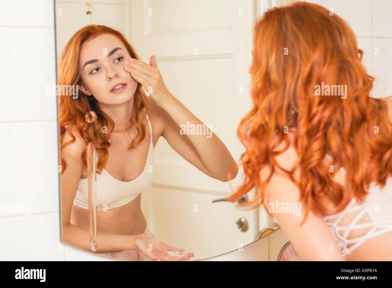 Woman applying face cream in bathroom - Stock Image