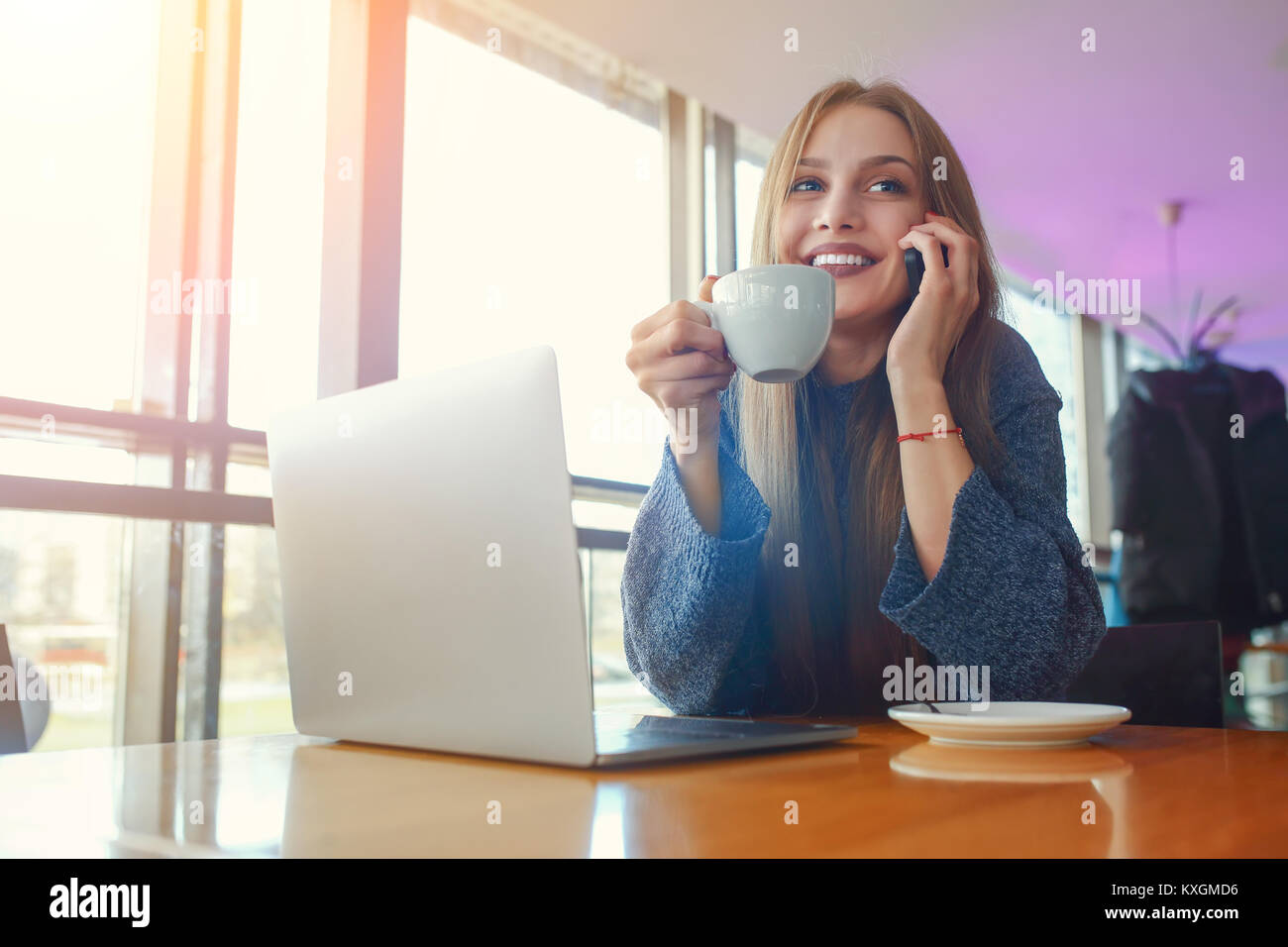 Happy young hipster woman with cup of cofe talking on the phone in at cafe. Laptop on the table. - Stock Image