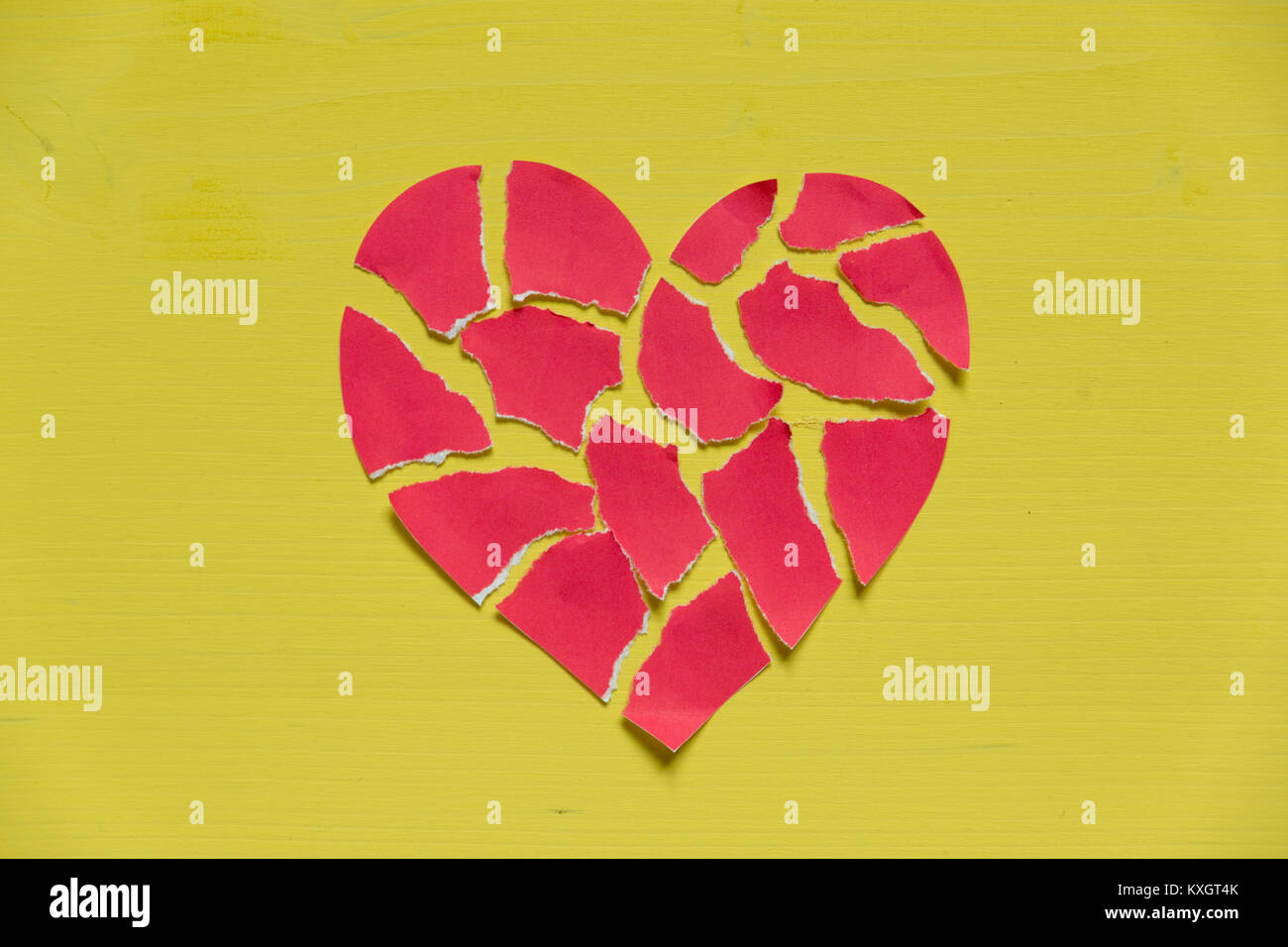 Crushed paper heart on yellow background. Broken heart concept - Stock Image