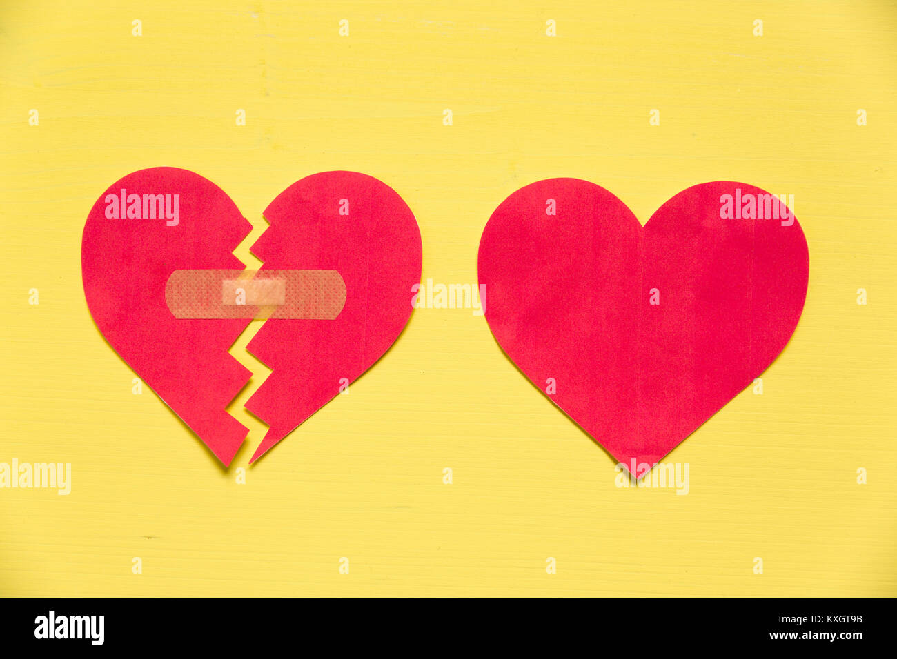 Broken paper heart with patch next to the whole paper heart on yellow background. Rebuild relationship concept - Stock Image