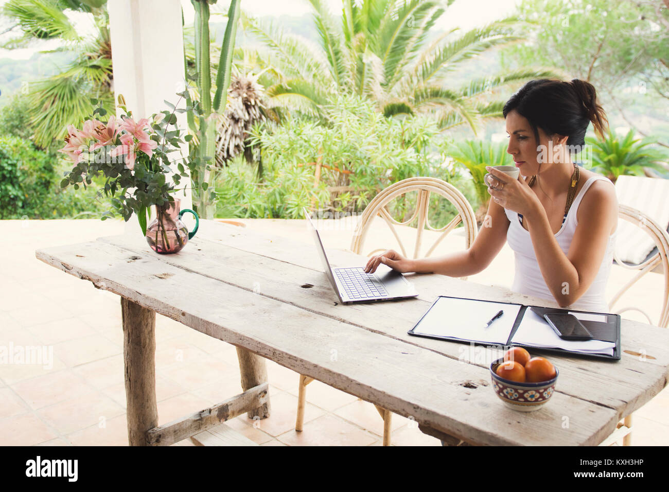 Beautiful woman teleworking outside in tropical location. - Stock Image