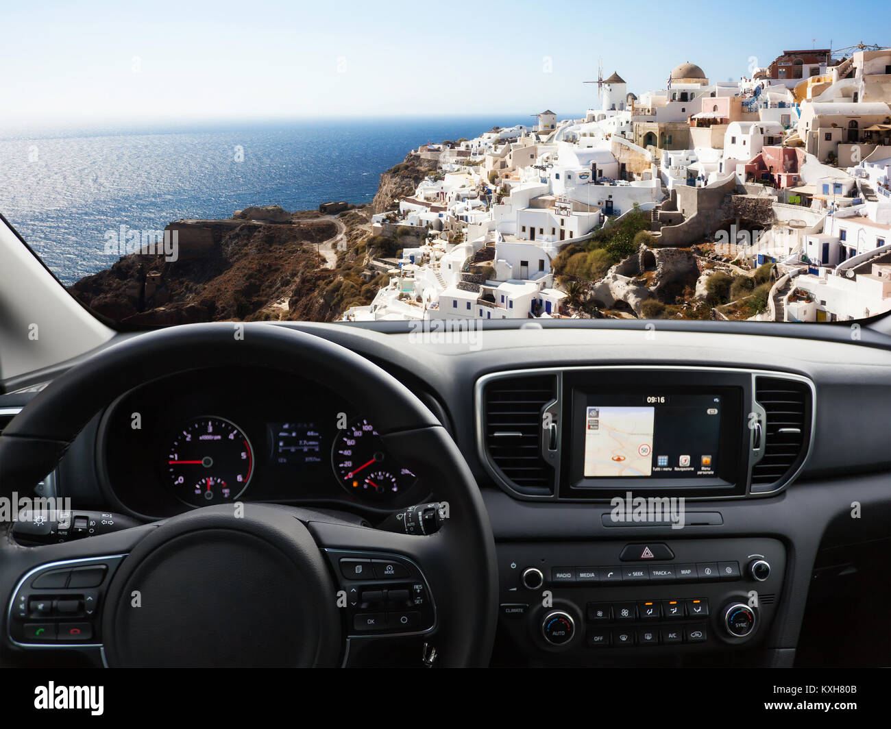 View of a car dashboard with a navigation unit traveling to Santorini Island. - Stock Image