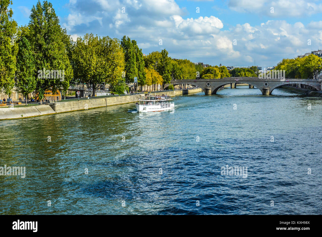A tour boat cruises along the Seine River near the center of Paris France on a sunny day in early autumn - Stock Image