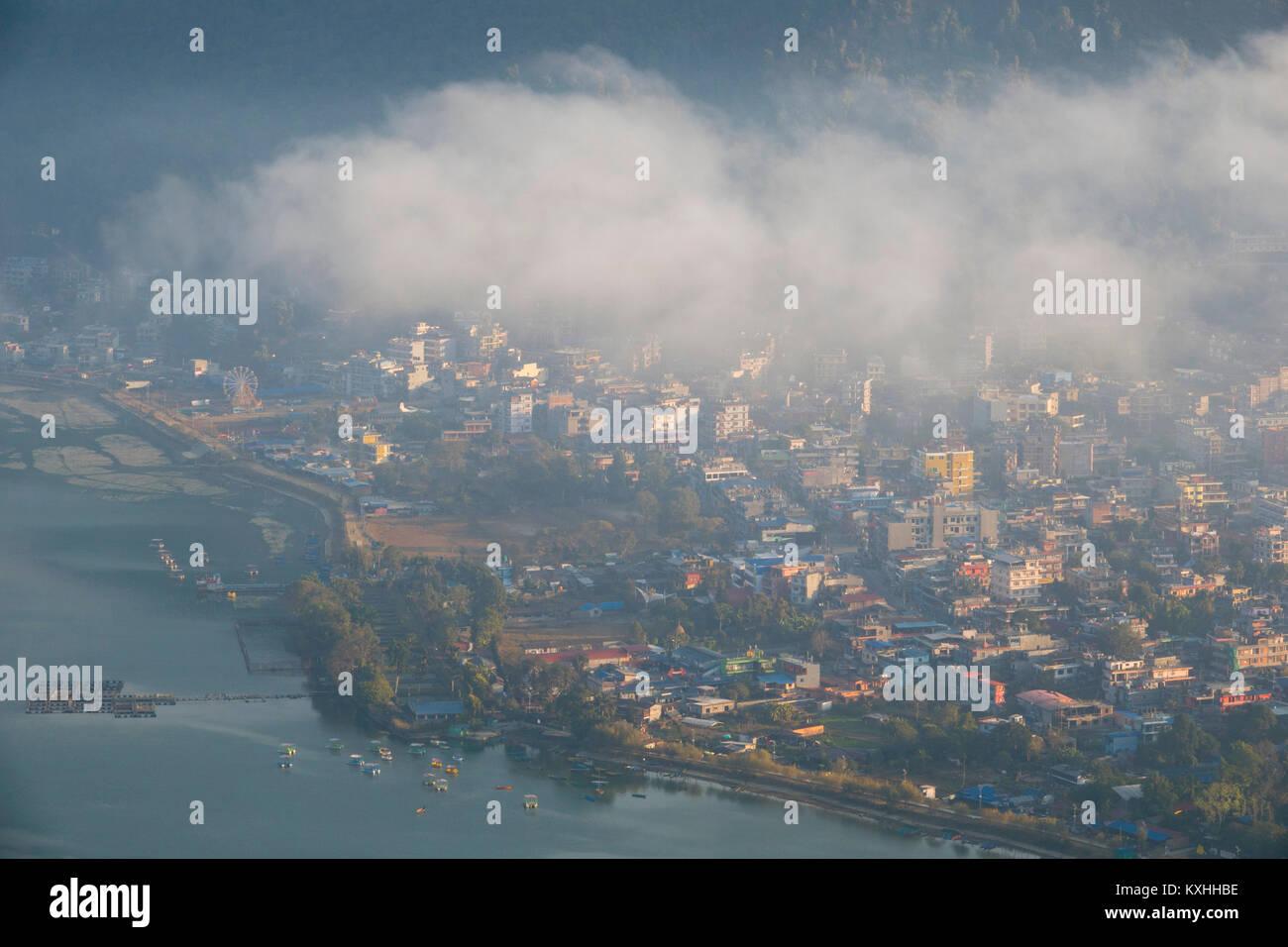 Early morning mist over Phewa Lake and Pokhara, Nepal - Stock Image