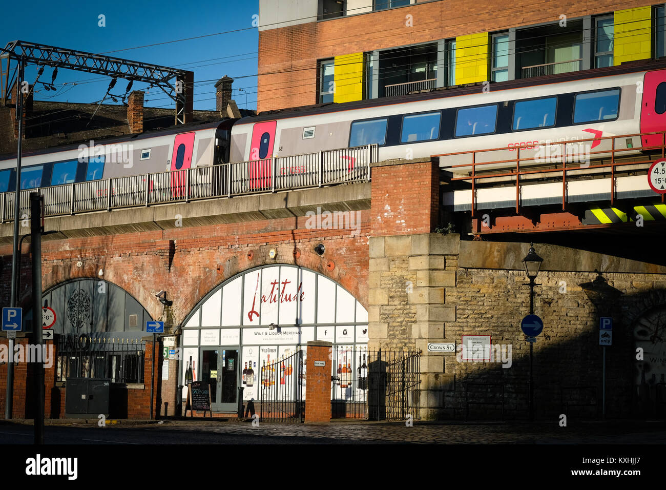 A CrossCounty train passing over shops and buildings on an elevate rail track in Leeds city centre, Yorkshire, UK - Stock Image