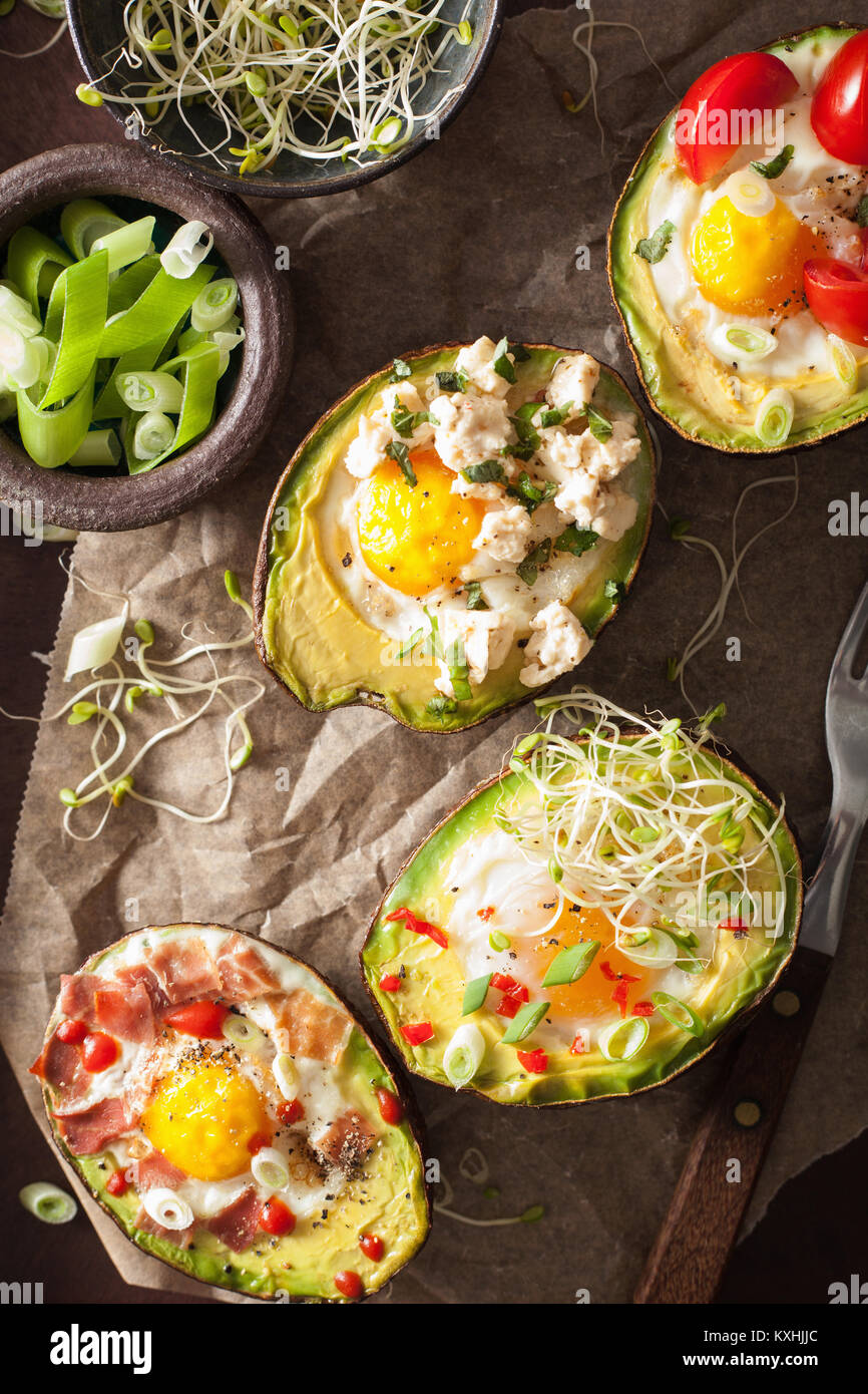 eggs baked in avocado with bacon, cheese, tomato and alfalfa sprouts Stock Photo