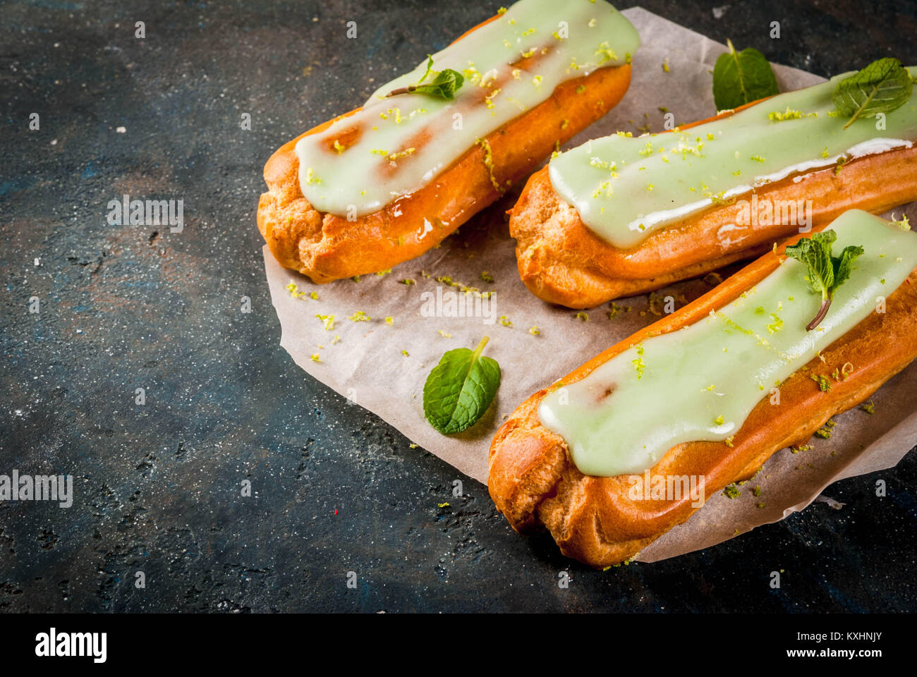 Traditional French dessert. Mojito Eclairs with lime zest and mint leaves, on dark blue background, copy space - Stock Image
