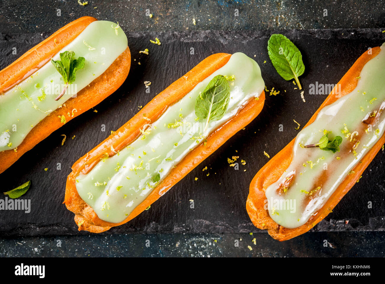 Traditional French dessert. Mojito Eclairs with lime zest and mint leaves, on dark blue background, copy space top - Stock Image