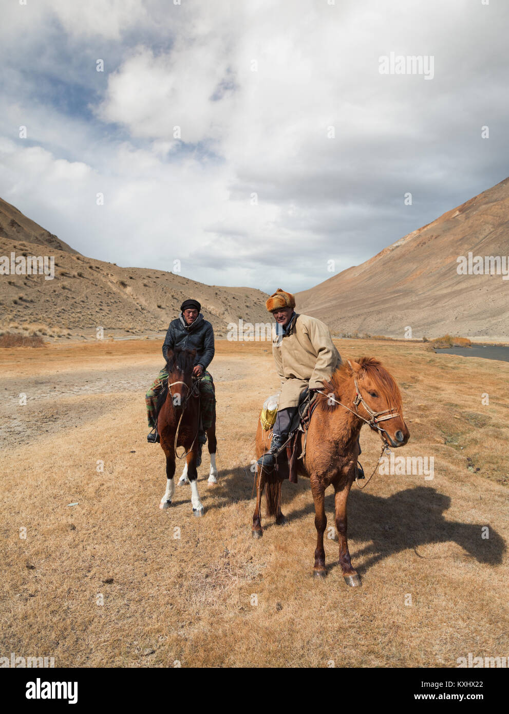 Mongolian horse riders resting next to river mountains Mongolia winter - Stock Image