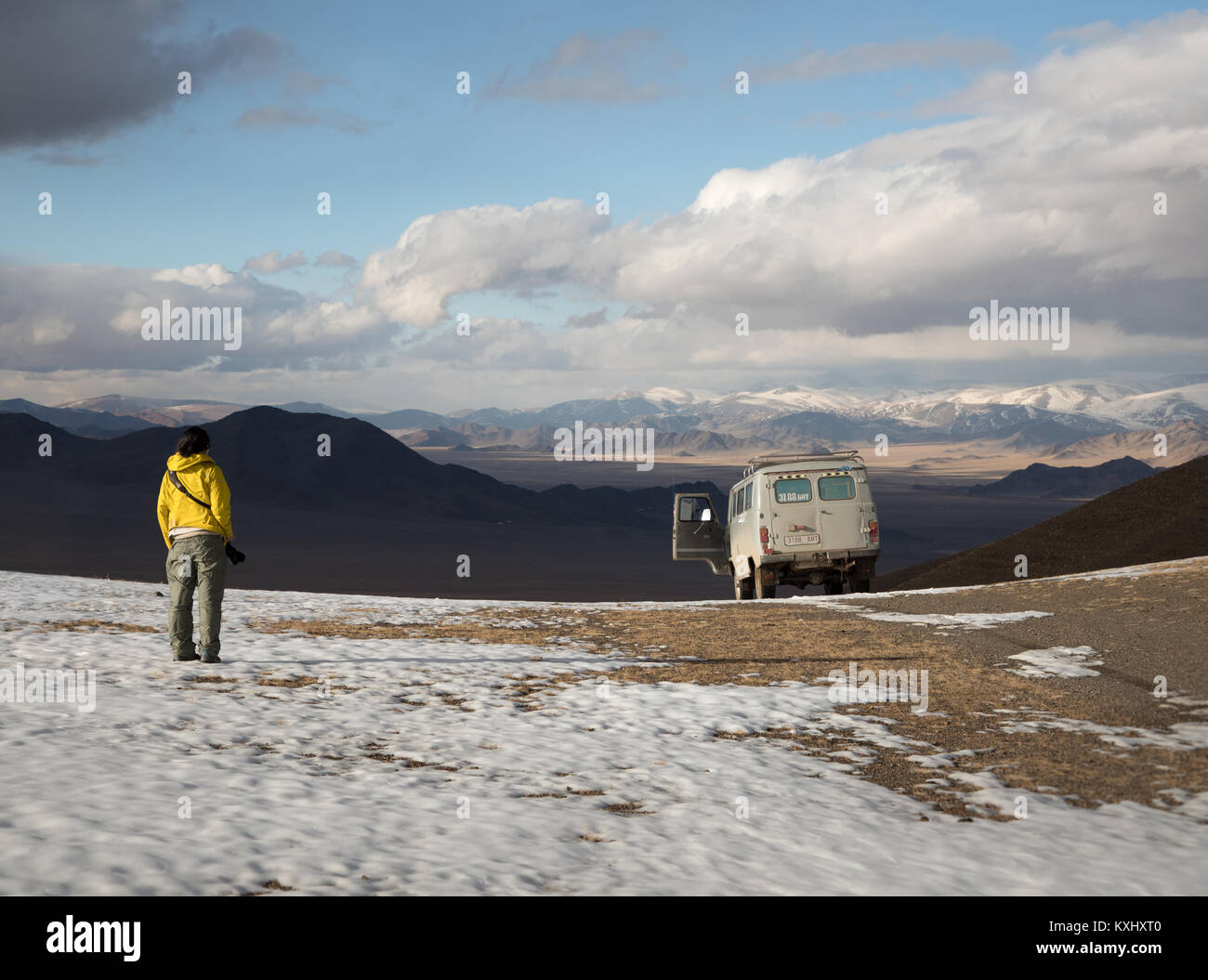 Girl woman looks out adventure camping site camper van Russian UAZ 452 Mogolian winter snow - Stock Image