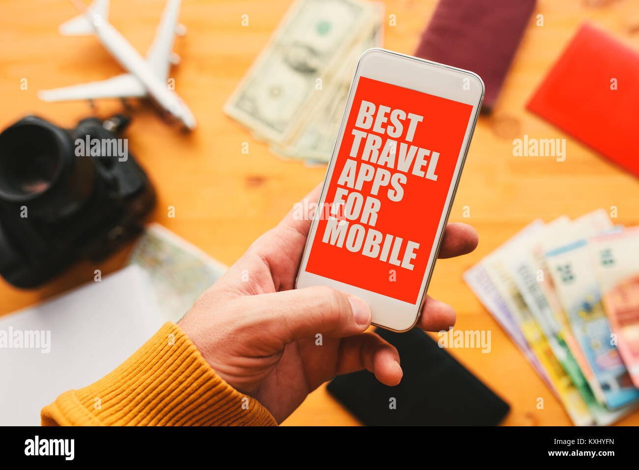 Best travel apps for mobile phone. Man holding smartphone with mock up application screen related to holiday vacation - Stock Image