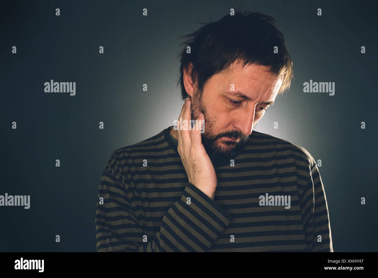 Depressed suicidal man thinking, melancholic adult guy with beard in dark room - Stock Image
