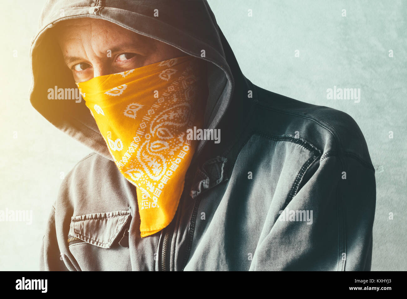 Hooded gang member criminal with scarf over face looking at camera, headshot portrait - Stock Image