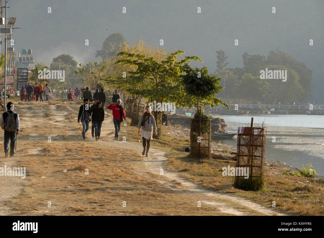 People walking along the edge of Phewa Lake in Pokhara, Nepal Stock Photo