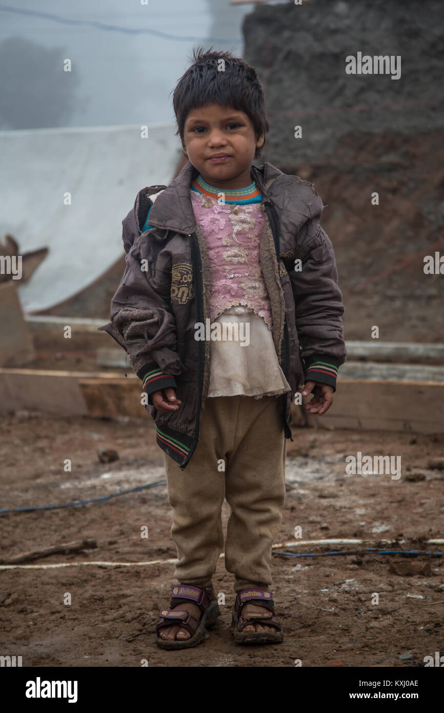 A portrait of a small kid looking in camera in north India. - Stock Image