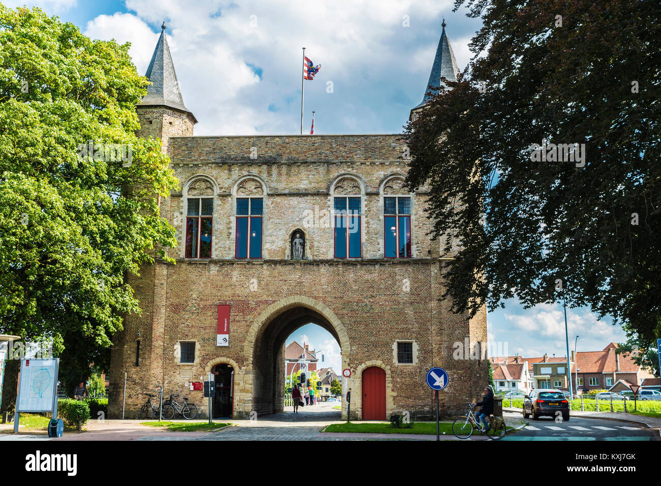 Bruges, Belgium, - August 31, 2017: Gentpoort (Gate of Ghent) with people circulating on bike in the medieval city Stock Photo