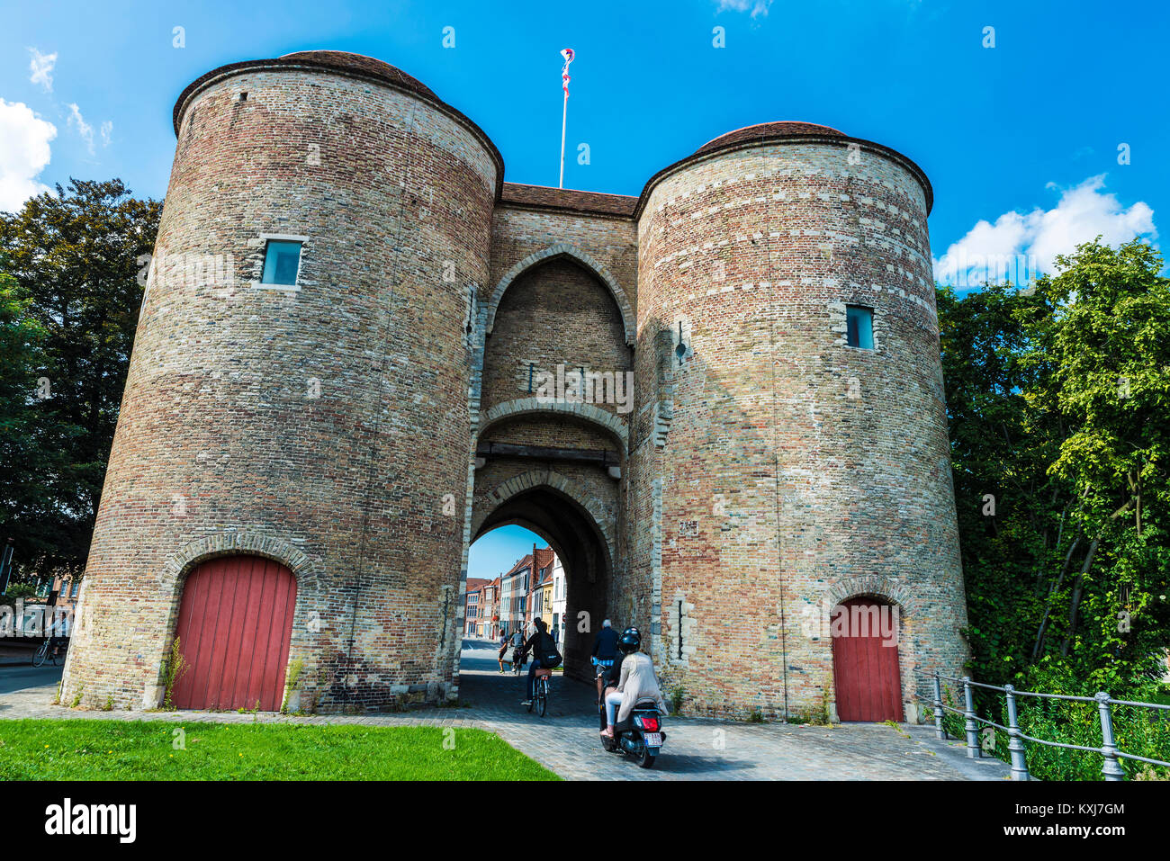 Bruges, Belgium, - August 31, 2017: Gentpoort (Gate of Ghent) with people circulating on bike and motorbike in the Stock Photo