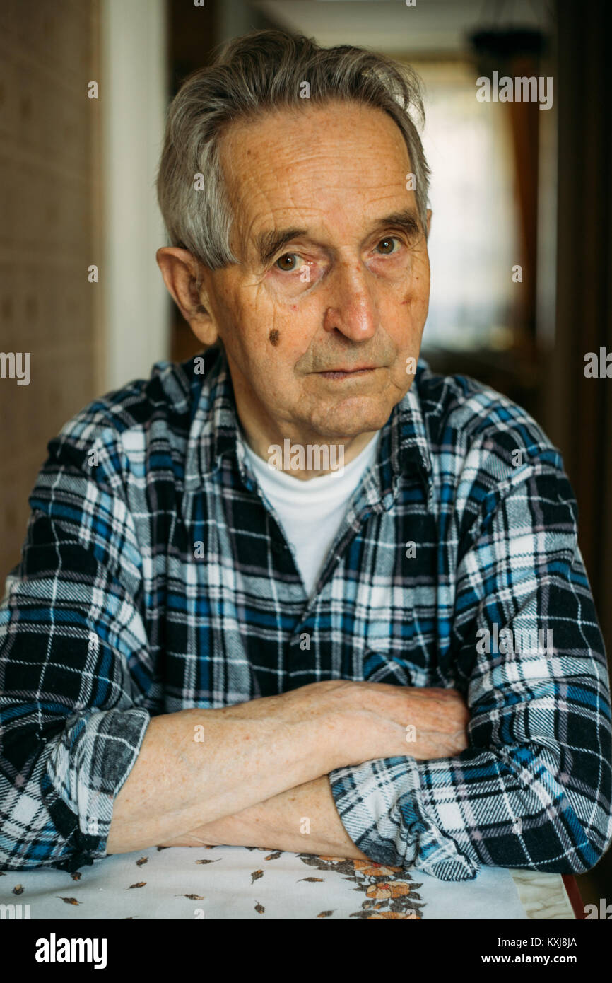 Portrait of an elderly senior man sitting and reflecting about the past - Stock Image