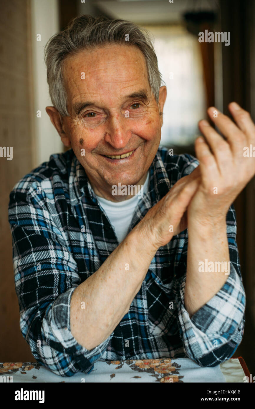 Portrait of an elderly senior man sitting and smiling - Stock Image