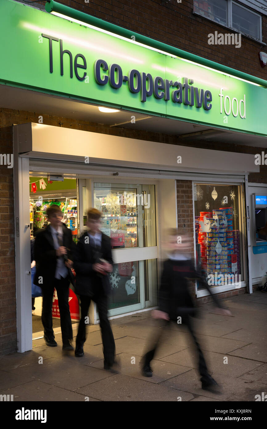 UK, England, Cheshire, Stockport, Bramhall, Dairyground Road, Co-op food store entrance at dusk, schoolchildren - Stock Image