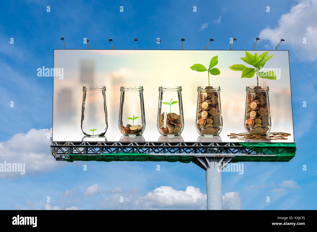 Billboard on beautiful sky showing the Gold coins and seed in clear bottle on cityscape photo blurred cityscape - Stock Image