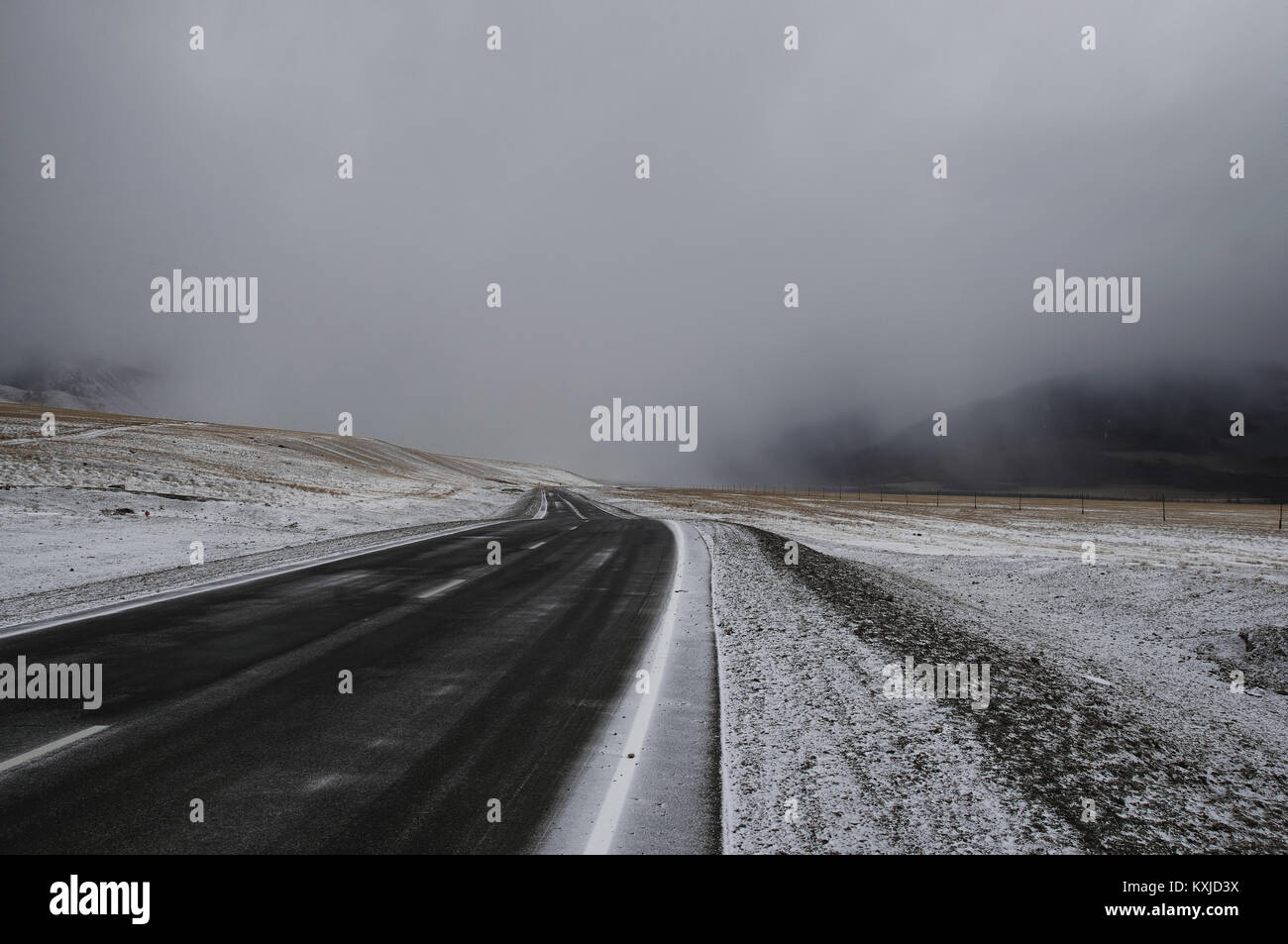 Road asphalt path on a winter snow desert wild mountain valley  at the background of the high peaks under a dramatic - Stock Image