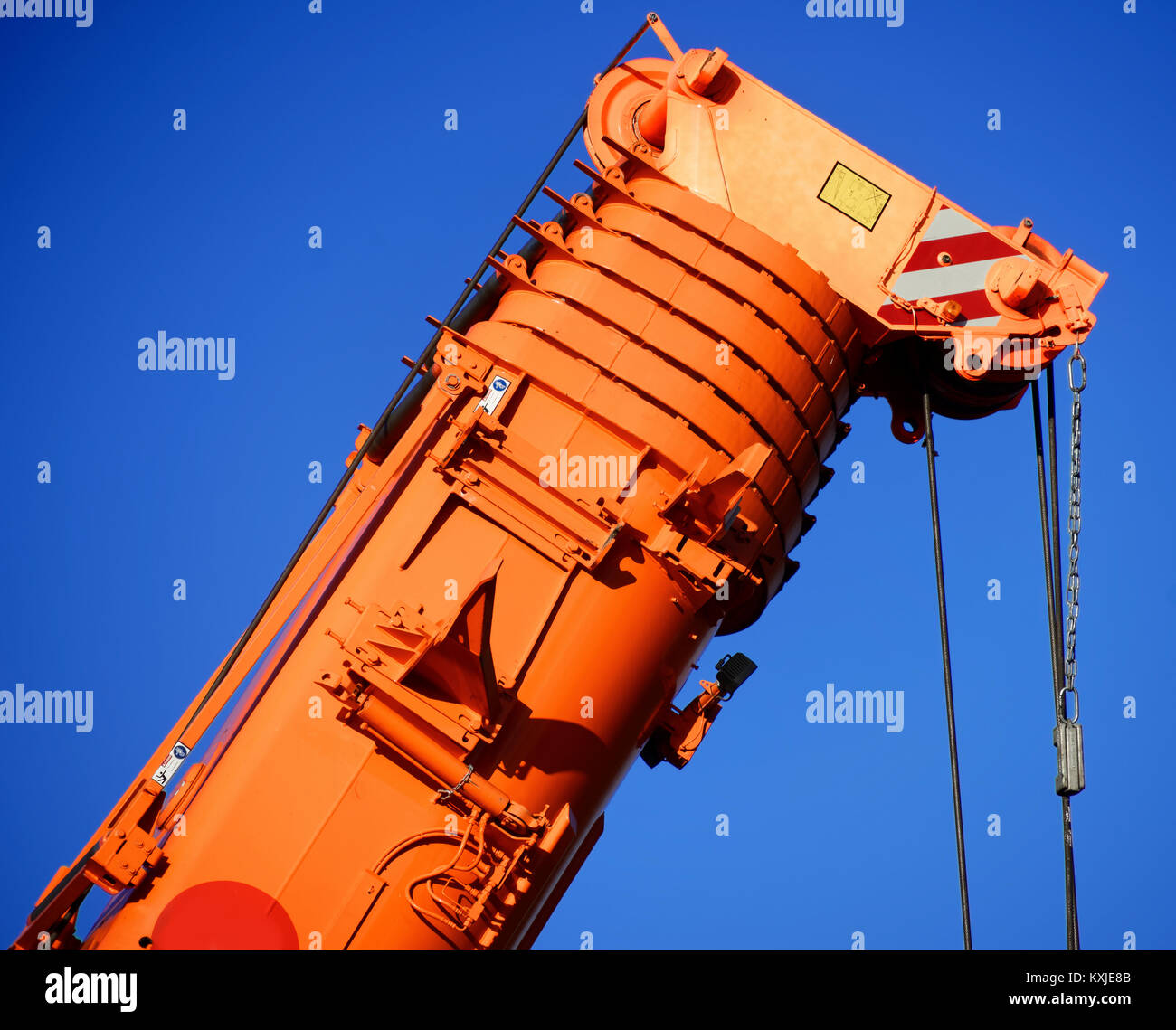 Zoom shot of an orange-coloured truck-mounted crane with telescopic boom pushed together, blue sky - Stock Image