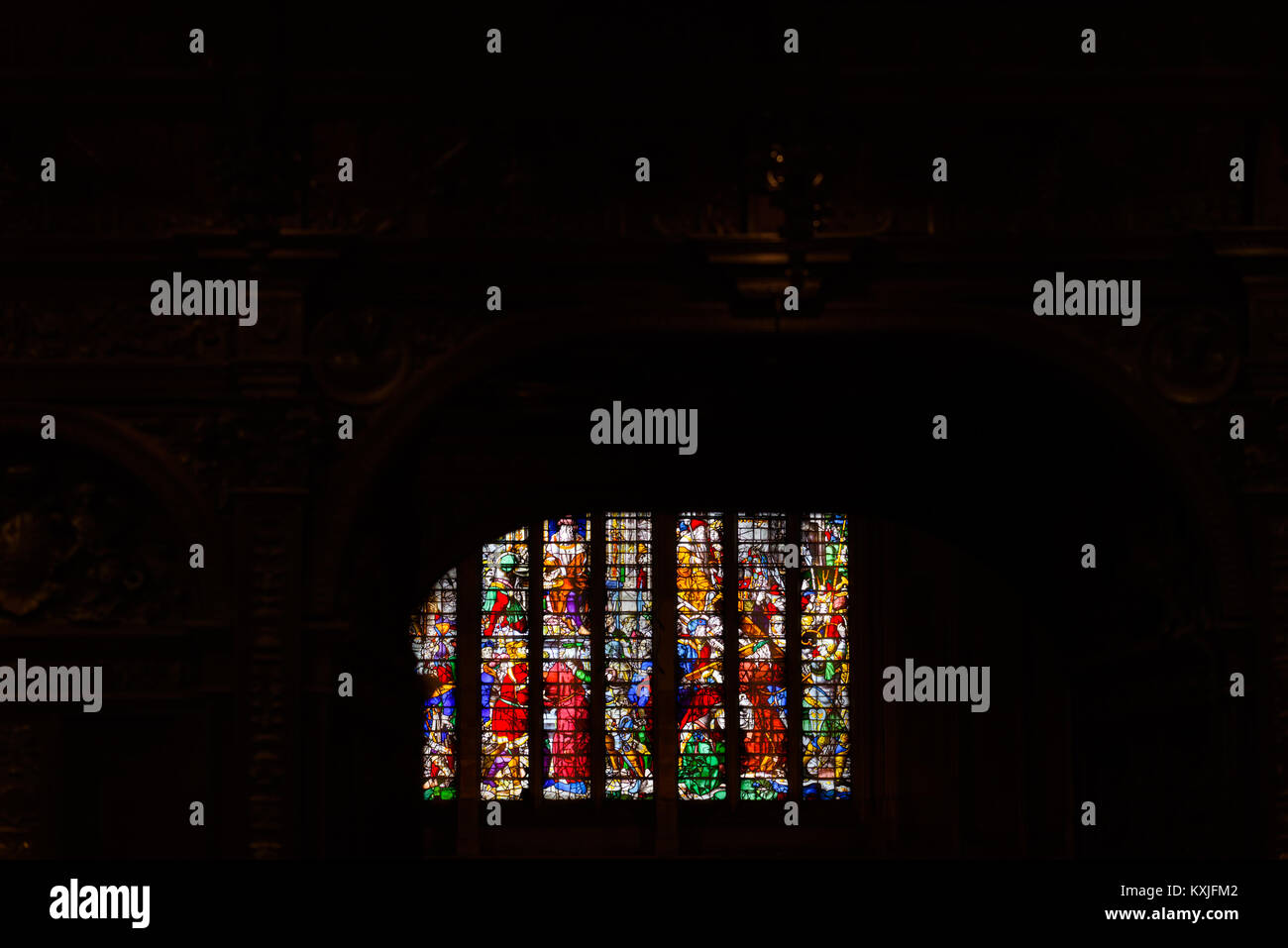 Stained glass window, illustrating the suffering and death of Jesus Christ, as seen via the rood screen in the chapel - Stock Image