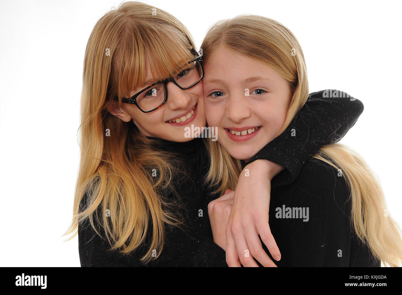 two pretty blonde Caucasian girls, smiling and hugging isolated on white - Stock Image