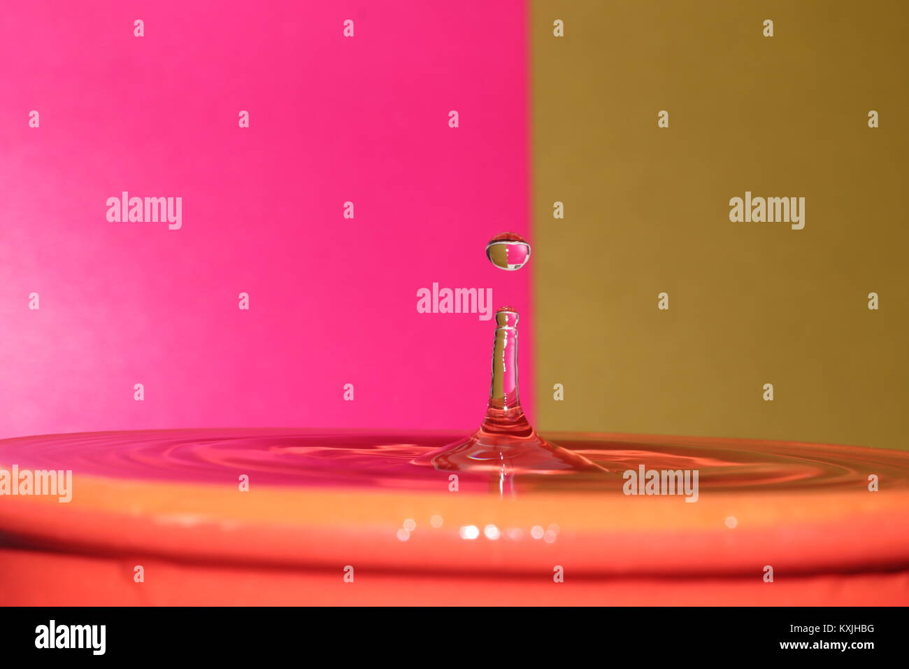 Water droplets two tone pink and yellow  colours create a stunning macro image rippling shimmering effect - Stock Image