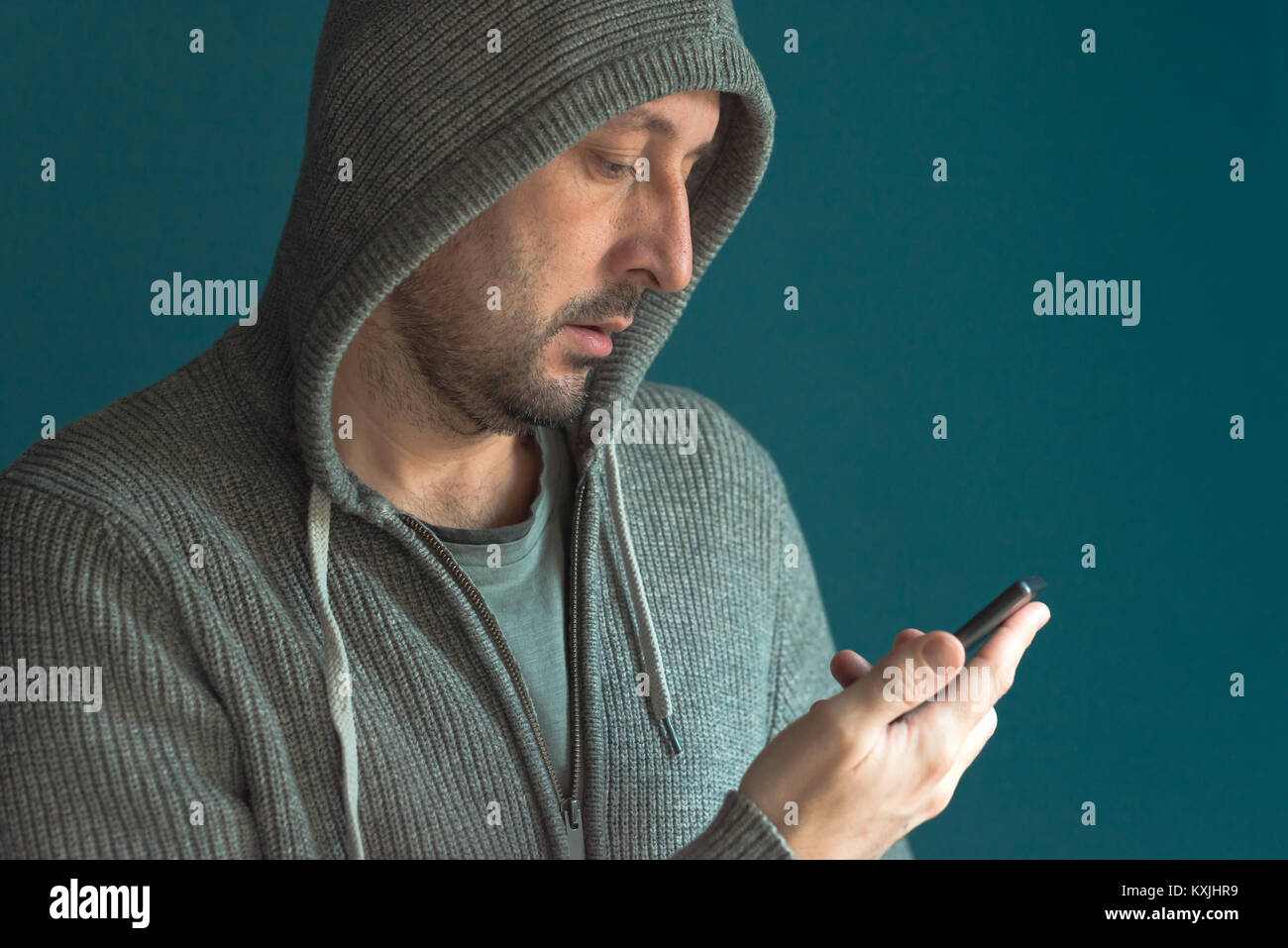 Casual man looking at mobile phone screen and reading app notification or sms text message - Stock Image