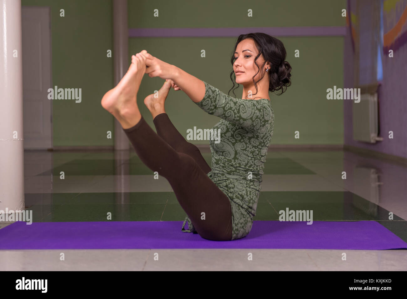 Girl doing yoga stretches in fitness class - Stock Image