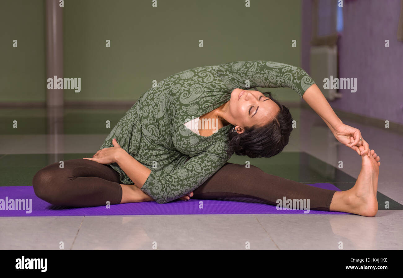 Yoga woman does exercises yoga in fitness class - Stock Image