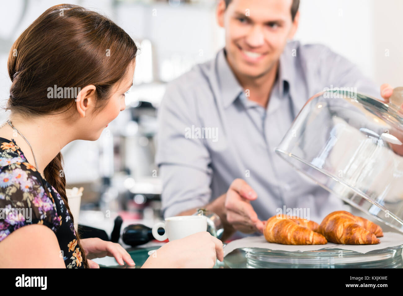 Friendly waiter offering to young female customer fresh French c - Stock Image