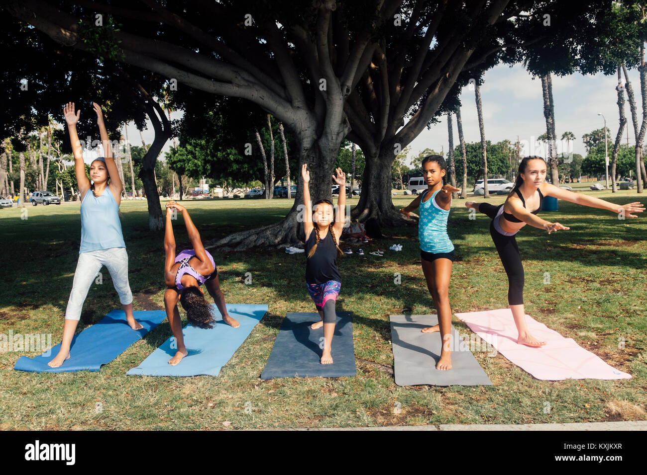 Girls and teenage schoolgirls practicing yoga warrior pose on school playing field Stock Photo
