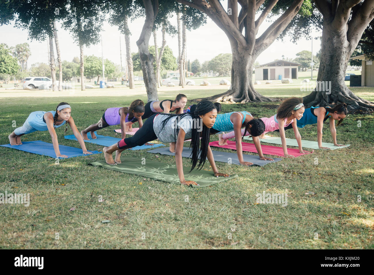 Schoolgirls practicing yoga plank pose on school sports field - Stock Image