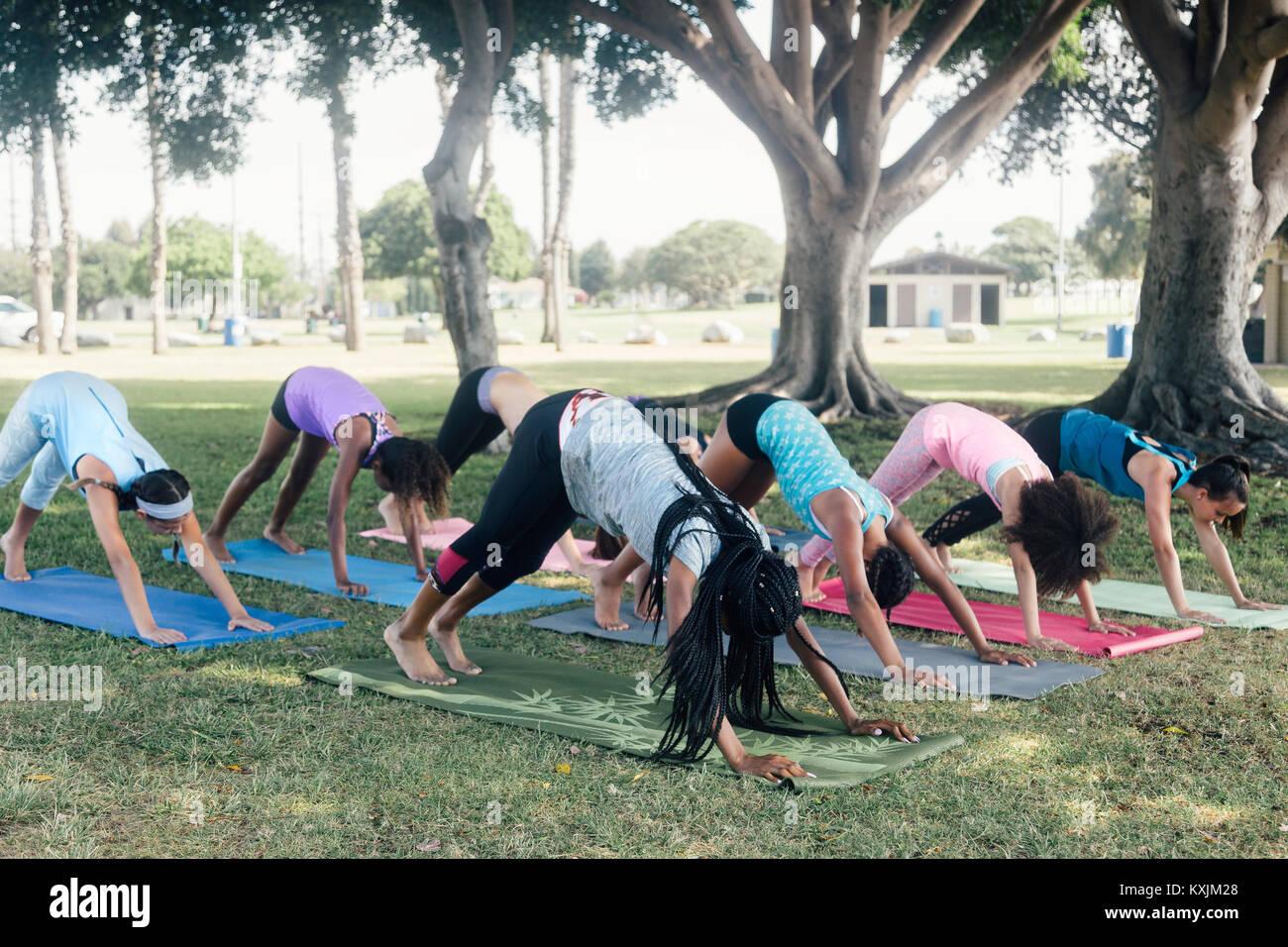 Schoolgirls practicing yoga downward facing dog pose on school sports field - Stock Image
