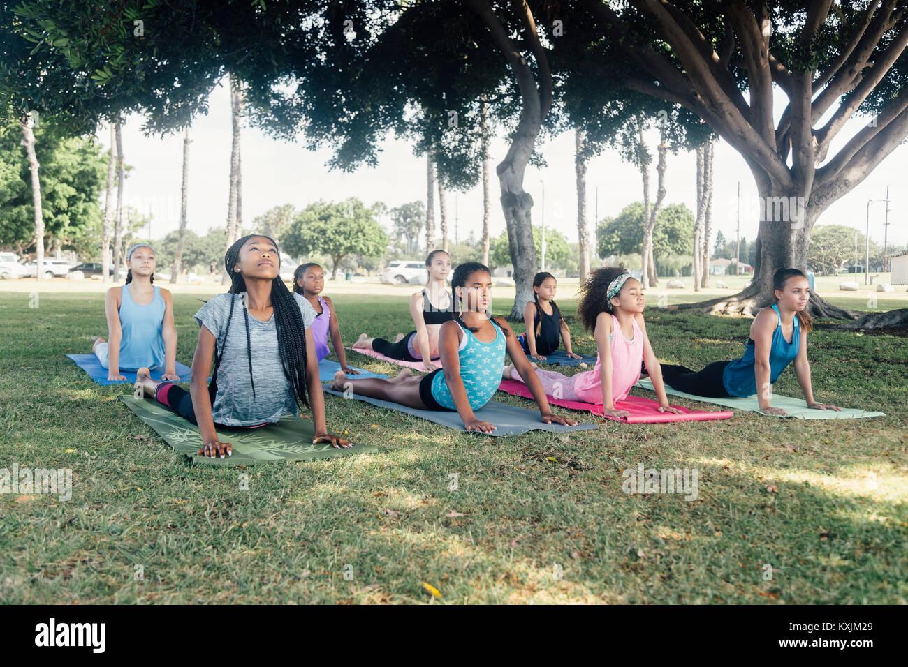 Schoolgirls practicing yoga upward facing dog pose on school sports field - Stock Image