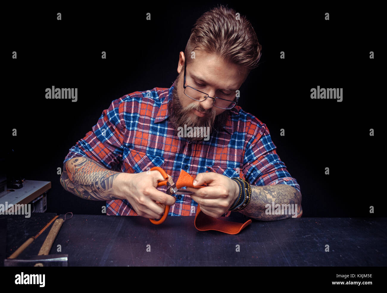Craftsman working with leather works with leather goods at his desk - Stock Image