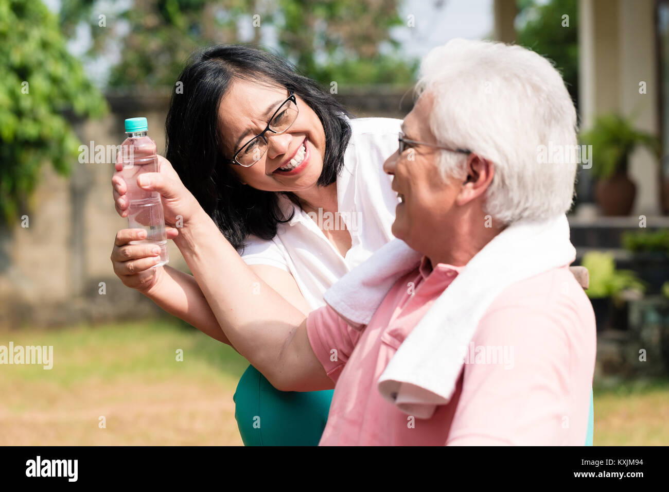 Careful senior woman giving a bottle of water to her partner out - Stock Image