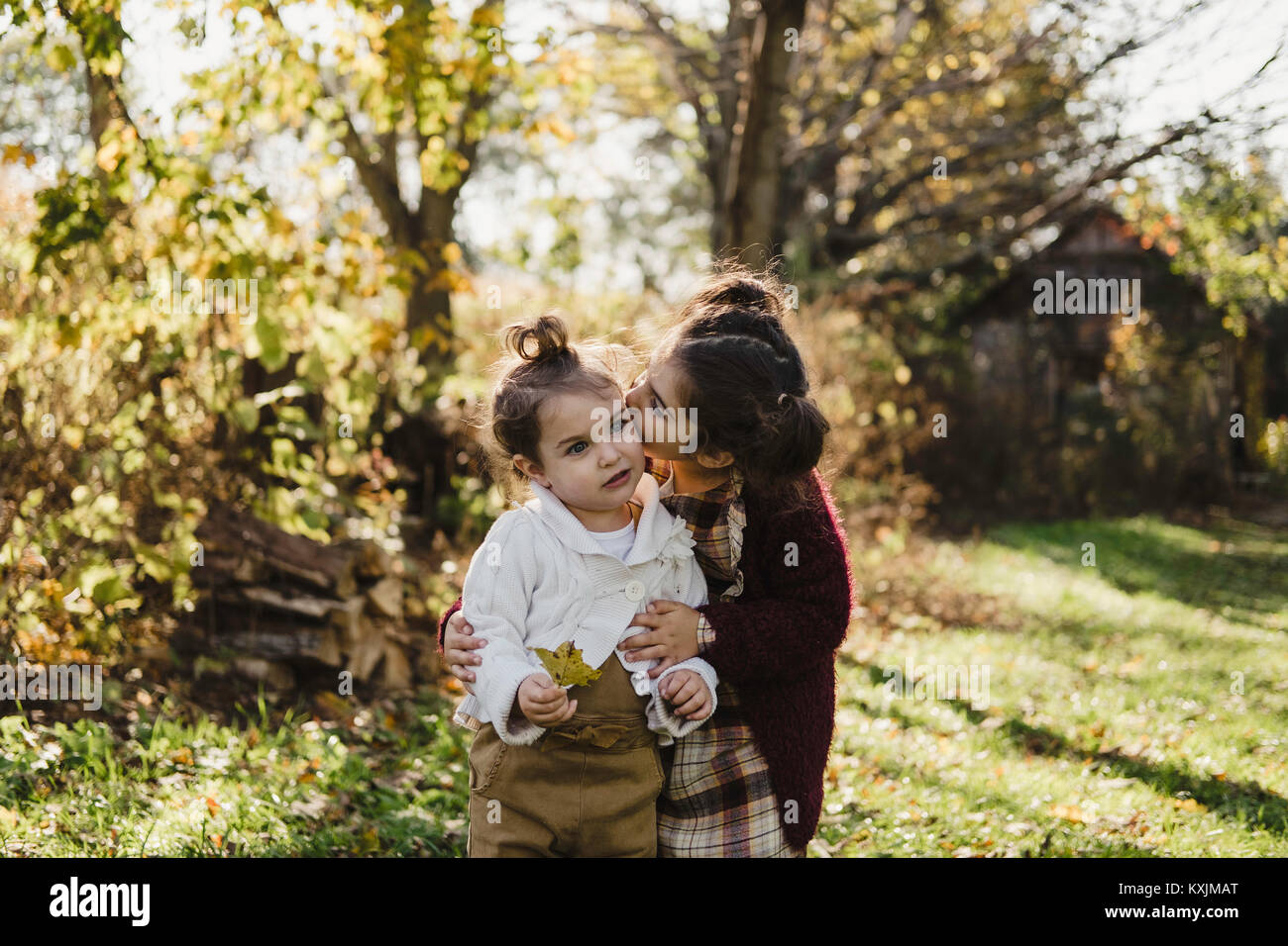 Girl hugging younger sister, in rural setting - Stock Image